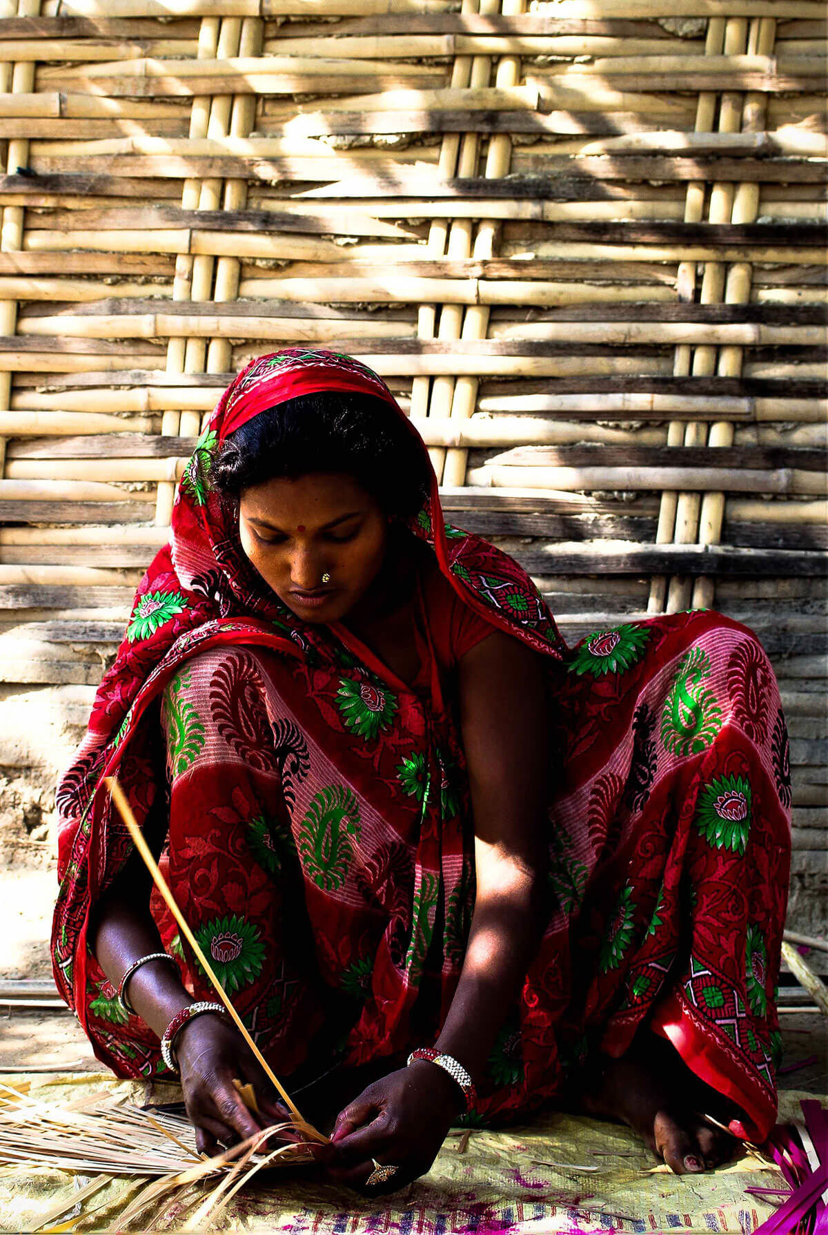 Babita Marik making fan or bena out of bamboo shoots. This is their traditional occupation which is slowly dying out. She only makes them when she gets orders, that is only during wedding seasons. She gets Rs 1000 per order. On other times, she stays home looking after her children. Mariks are of Dom caste, much lower than Dalits in the caste hierarchy.