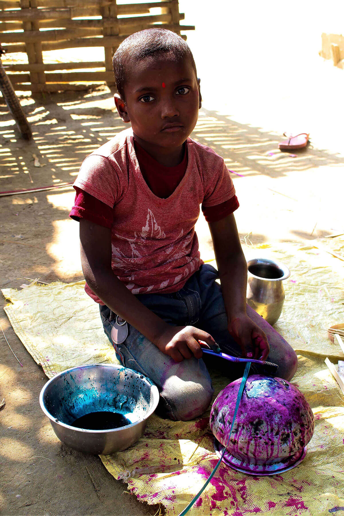 Babita Marik's another son helps his mother by painting the bamboo shoots.